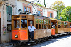 The tram is on street of Soller town. MALLORCA, SPAIN - JUNE 2: The tram is on street of Soller town and tourists are in outdoor restaurant on June 2, 2015 in Royalty Free Stock Image
