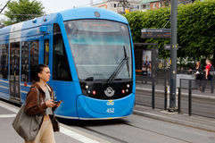 Tram in Sundbyberg. Sundbyberg, Sweden - June 21, 2016: Tram on street tracks in Sunbyberg city center with a woman walking at the tram stop Stock Photography
