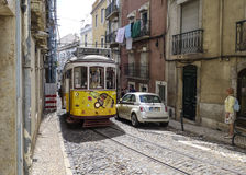 Tram, the symbol of the city in narrow street of Lisbon. Stock Photo