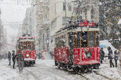 Tram und Leute im Alltagsleben unter Schnee regnen an Istiklal-Straße Lizenzfreies Stockbild