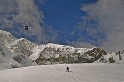 Tram und Skifahrer an der Gebirgsspitze stockfotografie