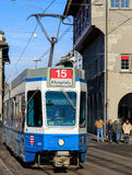 Tram in Zurich, Switzerland. Zurich, Switzerland - 29 January, 2017: a tram passing along the Limmatquai quay, pedestrians on the walkway. Trams have been a royalty free stock image