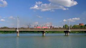 Trambewegingen langs de brug over de rivier op achtergrond van installatie en blauwe bewolkte hemel stock video