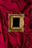 Trame d'or sur le satin rouge Photos stock