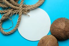 Trame d'?t? Cadre de papier pour votre texte, noix de coco et corde marine sur un fond bleu-clair lumineux Vue sup?rieure image libre de droits