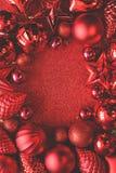 Trame rouge de Noël Boules, étoiles, cônes et coeurs de Noël sur le fond rouge d'étincelles Configuration plate Vue supérieure images stock