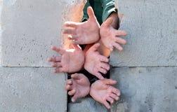 Tramite i blocchi rotti nel muro di cemento disteso le mani degli immigrati dei rifugiati che chiedono l'acqua e l'alimento immagine stock