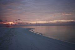 Tramonto ad una spiaggia della località di soggiorno alle Maldive Fotografie Stock Libere da Diritti