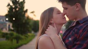 Tramonto adolescente dolce di bacio dell'abbraccio delle coppie di confessione di amore stock footage