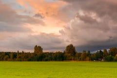 Tramonto al campo con le nuvole scure nella tonnellata drammatica Immagini Stock