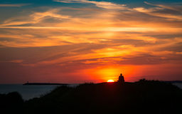 Tramonto alla costa con la siluetta di meditare dell'uomo Fotografia Stock