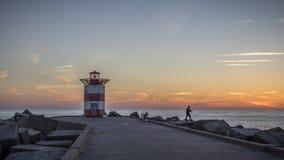 Tramonto alla spiaggia L'aia di Scheveningen del faro Fotografia Stock Libera da Diritti