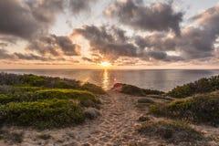 Tramonto alla spiaggia scenica di Scivu - dune di sabbia con la vegetazione del mirto con l'oceano nei precedenti e nelle nuvole  fotografie stock