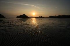 Tramonto alla spiaggia in una bassa marea quando il fondo del mare è visibile Fotografie Stock