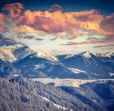 Tramonto alpino di inverno nelle montagne con il cielo drammatico Fotografia Stock