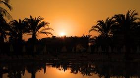 Tramonto arancio con la riflessione delle palme e di Sun su acqua Fotografia Stock Libera da Diritti