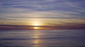 Tramonto arancio del paesaggio con il sole riflesso nell'acqua e nel cielo blu luminoso stock footage