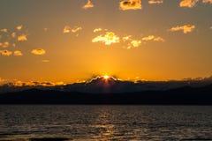 Tramonto arancio dietro le nuvole/montagne fotografie stock libere da diritti