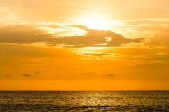 Tramonto arancio nuvoloso sopra il mare fotografia stock libera da diritti
