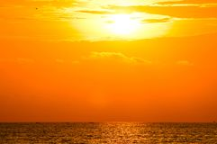 Tramonto arancio nuvoloso sopra il mare immagine stock