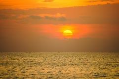 Tramonto arancio nuvoloso sopra il mare Il sole arancio è parzialmente obscu immagine stock