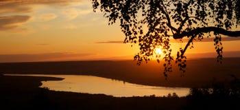 Tramonto arancio sopra il fiume Immagine Stock