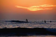 Tramonto arancio sopra il Pacifico con i pagaia-pensionanti fotografie stock libere da diritti