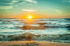 Tramonto arancio su una spiaggia Fotografia Stock Libera da Diritti