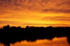 Tramonto arancione sopra il fiume Immagini Stock