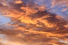Tramonto ardente con le nuvole ed il cielo blu arancio Immagini Stock