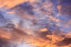 Tramonto ardente con le nuvole ed il cielo blu arancio Fotografie Stock
