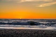Tramonto attraverso la spuma pacifica La cima delle onde sta essendo scarica davanti al sole immagini stock