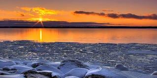 Tramonto attraverso un lago congelato fotografia stock