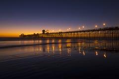 Tramonto brillante della spiaggia con il pilastro Fotografie Stock