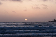 Tramonto in cielo nuvoloso con le onde di oceano Immagine Stock