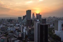 Tramonto in Città del Messico con una vista di traffico e di costruzioni a Paseo de la Reforma fotografia stock libera da diritti