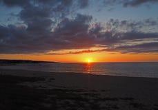 Tramonto con il sole arancio rosso che va giù al mare sulla sabbia fotografie stock