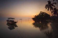 Tramonto con la barca del pescatore alla spiaggia Fotografie Stock Libere da Diritti