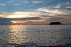 Tramonto con la nave e la piccola isola immagini stock