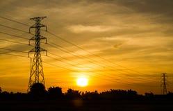 Tramonto con la torre elettrica della trasmissione Immagine Stock
