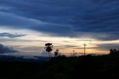 Tramonto con le nuvole di pioggia e la posta di elettricità della siluetta Fotografie Stock Libere da Diritti