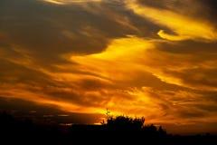 Tramonto con le nuvole drammatiche ed i colori Fotografia Stock