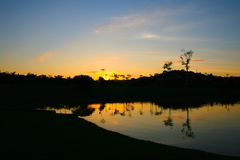 Tramonto con le riflessioni nel lago park fotografia stock