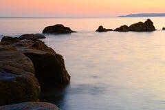 Tramonto con le rocce ed il mare Fotografia Stock