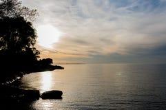 Tramonto costiero con una riflessione piacevole e un piccolo lato della siluetta a sinistra dell'immagine Fotografia Stock