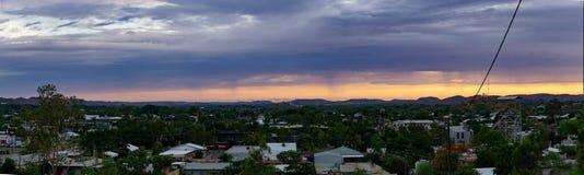 Tramonto d'ardore sopra una città con il soffitto grigio-porpora della nuvola fotografia stock