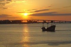 Tramonto davanti al ponte, con la nave di pirata Immagini Stock