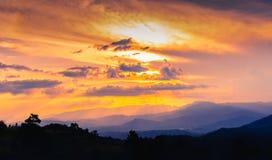 Tramonto del colourfull e drammatico con le montagne e la foresta fotografia stock