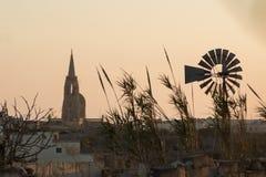 Tramonto del mulino a vento in spiaggia di Malta fotografia stock