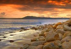 Tramonto dell'arancio della spiaggia rocciosa   Immagine Stock